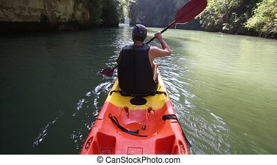 old man paddles on kayak down river among sun light and...
