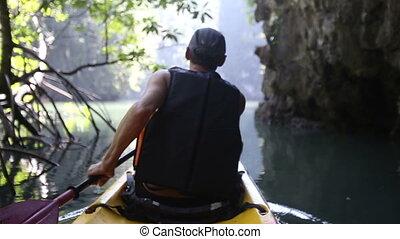 man backside view rows on kayak in canyon - european man...