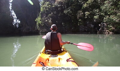 man backside view in life-vest rows to river mouth in canyon...