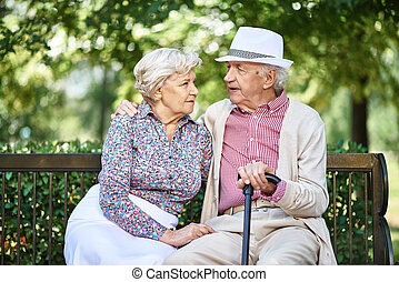 Restful seniors in smart casual sitting on bench in park and...