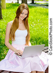 in the park - Smiling young woman sitting in the park on a...