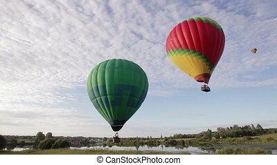 Hot air balloons flying over lake and field