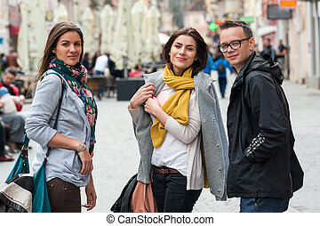 Cheerful group of friends walking the city street talking...