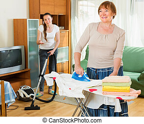 girl helps her mature mother with cleaning - Young girl...