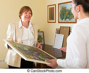 Adult females looking at the picture in art gallery