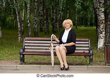Elderly business woman in jacket sittin on bench in summer...