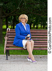 Mature business woman in a jacket with diary sitting on a...