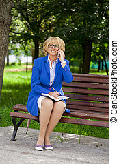 Elderly business woman in jacket sittin on bench with daily...