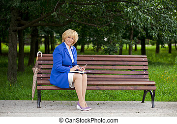 Elderly business woman in jacket sittin on bench with daily log