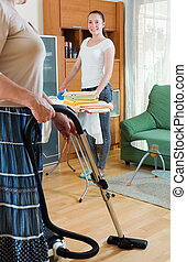 Smiling girl with iron helps her mother do housework