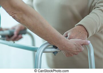 Medic helping patient with zimmer - Close up of medic hands...