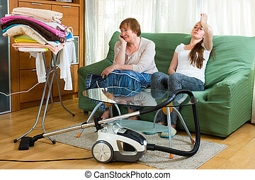 Two women having a rest after cleaning - Two adult women...