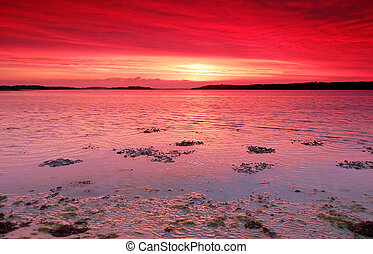 Red sunset over the sea - A dramatic red sunset over the...