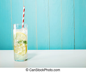 Iced lemonade with big red striped straws on pastel blue...