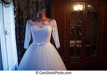 White wedding dress hanging on a mannequin in a room