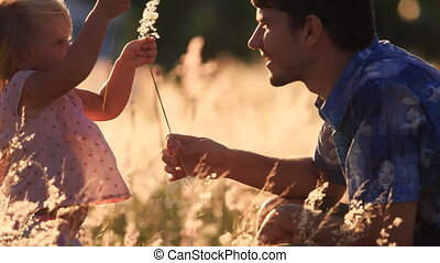 father shows small daughter field flower in meadow -...