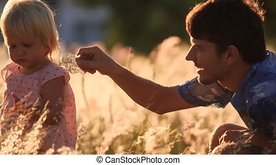 father small daughter play with field flower in meadow -...