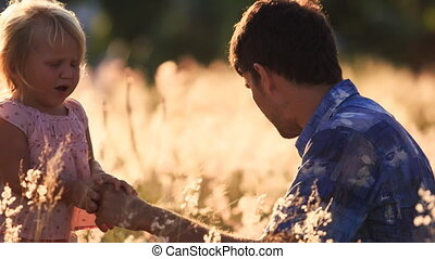 father shows small daughter field flowers under sunrays -...