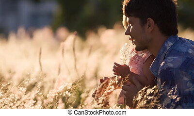 father and small daughter play laugh with field flower -...