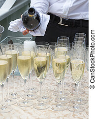 champagne in glass glasses - unrecognizable waiter pours a...