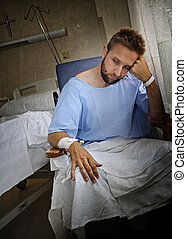 young injured man in hospital room sitting alone in pain...
