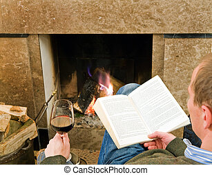 Relaxing by the fire - Man reading a book and drinking a...