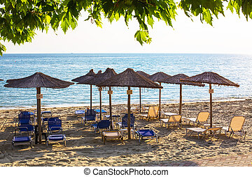 Row of wooden umbrellas at sandy beach, sea during the...