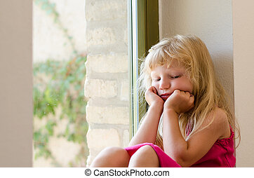 bored girl with long blond hair sitting by the window -...