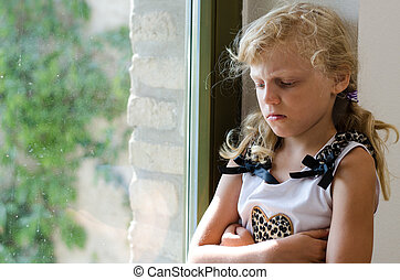 angry girl with long blond hair sitting at the window