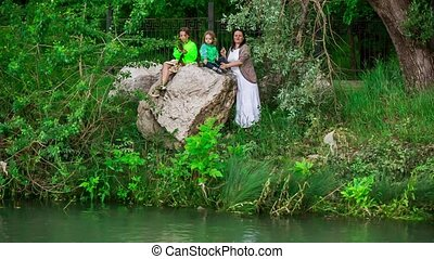 Mother And Two Children Throwing Stones Into Pond - This is...