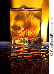 Glass with alcohol against fire with reflexion, in a glass...