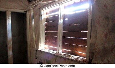 Sun penetrates through barred Windows in an abandoned house