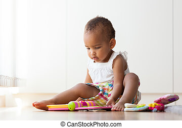 Portrait of little African American little girl sitting on...