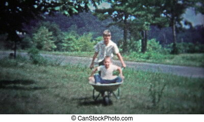 TENNESSEE, USA - 1953: Boys playing with wheelbarrel -...