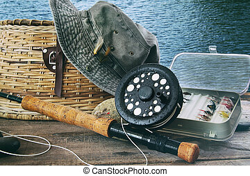 Hat and fly fishing gear on table near the waters edge