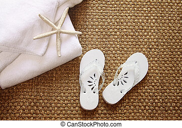 Spa sandals on seagrass mat with towels