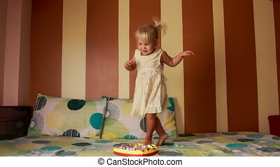 little blonde girl in white goes around new toy on sofa