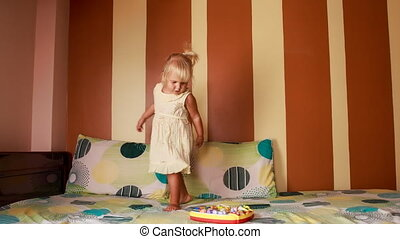 little blonde girl dances around new toy on sofa