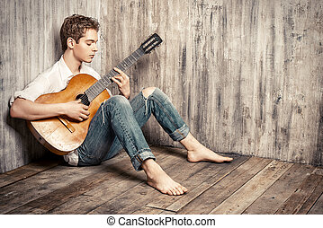 guy with guitar - Romantic young man playing an acoustic...
