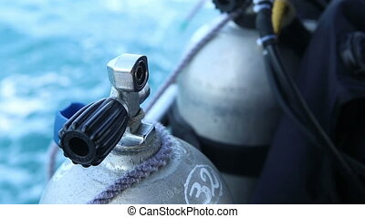 assistant unbinds oxigen cylinder for diving from boat -...