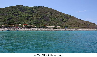 tourists swim on island beach against restaurants - tourists...