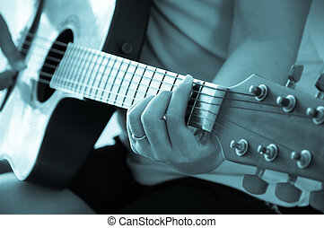 Woman playing acoustic guitar, blue tone