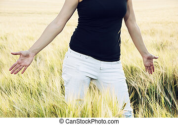Woman is smoothing the wheat cobs in the field Body part