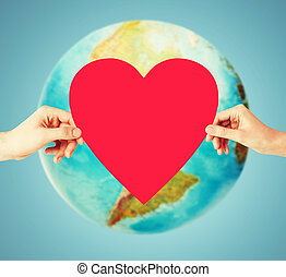 human hands holding red heart over earth globe - people,...