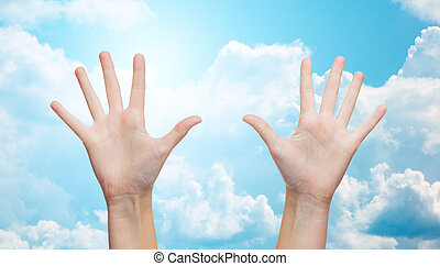 two woman hands making high five over blue sky - gesture,...
