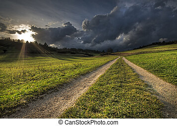 Storm - Country Road with sun shining through Rainy Clouds
