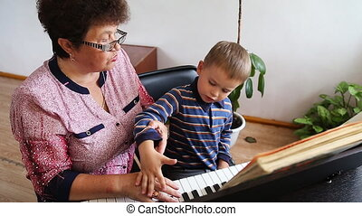 Boy learning how to the play piano with teacher