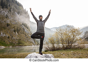 Man practicing yoga, performing a tree pose - Man practicing...