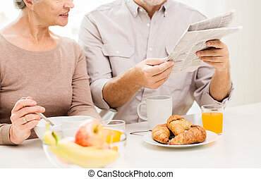 happy senior couple reading newspaper at breakfast - family,...