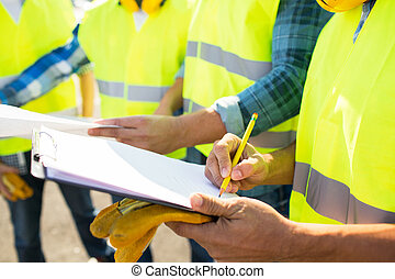 close up of builders in vests writing to clipboard -...